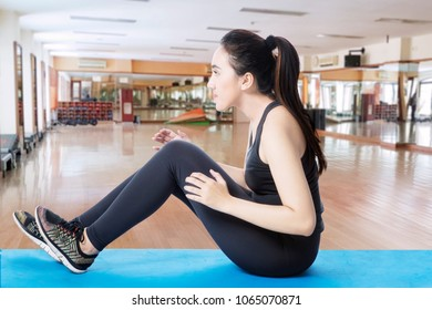 Side view of Arabian woman wearing sportswear while doing crunches in the fitness center