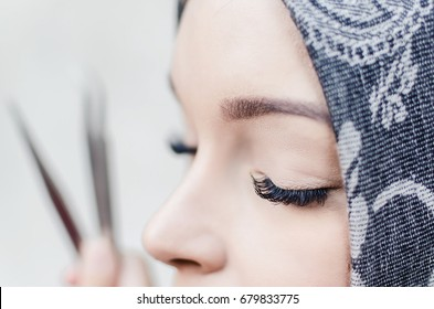 side view of arabic woman cropped face, eye lash extension macro shoot, tweezers and instruments on the background, long lashes, beautiful eyelashes extensions