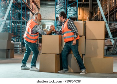 side view of arm wrestling of warehouse workers on boxes