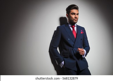 side view of an arrogant stylish man in suit and tie posing in studio, looking to a side