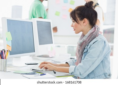 Side view of an artist using computer with colleagues behind at the office