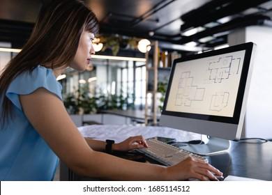 Vue latérale d'une femme d'affaires asiatique portant des vêtements et des lunettes intelligentes, travaillant dans un bureau moderne, assise sur un bureau et utilisant son ordinateur.