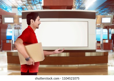 Side view of asian delivery man send a parcel on the building