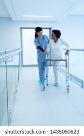 Side view of Asian female doctor with stethoscope around the neck helping mature mixed-race female patient to walk with walker in the corridor at hospital.