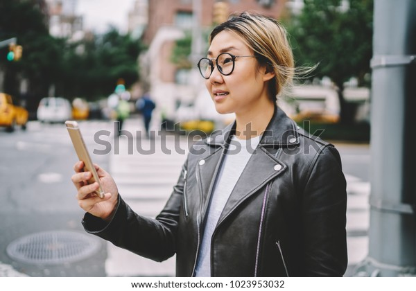 Side view of asian female traveler in eyeglasses standing on street searching way for location using navigating application on phone, chinese woman reading notification on mobile strolling in city