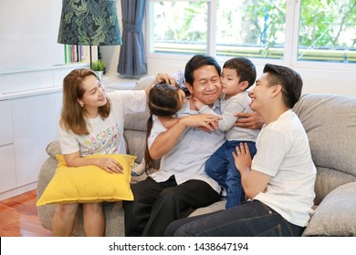 side view of asian granddaughter and grandson pecking grandfather on his cheek with asian father and mother on sofa in living room with happy and smiling face