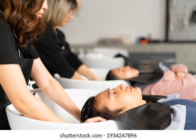 Side view of Asian male client relaxed lying on hair washing bed having hair washed with water by Asian female hairdresser with blurred background of another hairdresser washing client's hair in salon