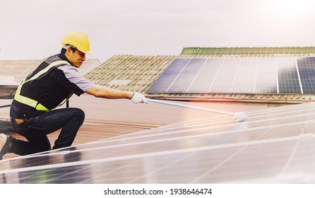 Side view Asian technicians cleaning blue outdoor solar photovoltaic panels to optimize functionality : Cleaning and inspection of solar panels on the roof of industrial plants : Selective focus