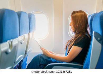 Side view of Asian woman using tablet in plane cabin.