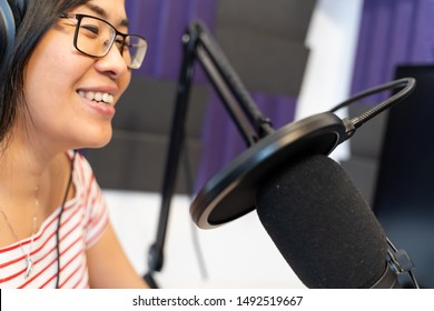 Side view of a asian woman wearing glasses and recording a podcast at the radio station.