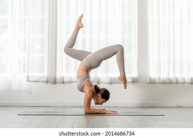 Side view of Asian woman wearing green sportwear doing Yoga Balance exercise in front of windows,Yoga HandStand pose or Pincha Mayurasana,Calm of healthy woman breathing and meditation yoga at home
