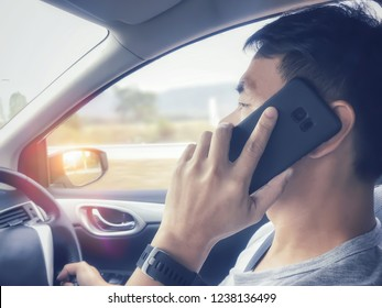 Side view of Asian young man using mobile phone, smartphone while driving a car with single hand.