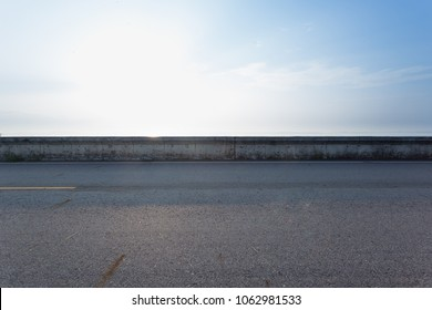 The side view of the asphalt sloping road with the edge of the sky is a bright and empty sky.