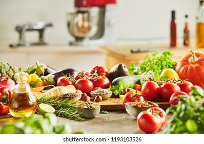 Side view of assorted vegetables including tomatoes and pumpkins covering cutting board in front of kitchen