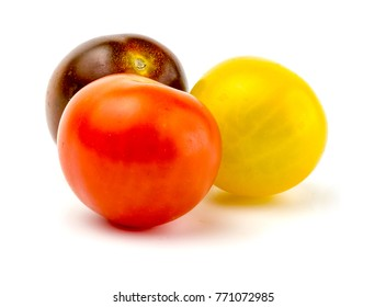 Side view of assortment of cherry tomatoes on white background