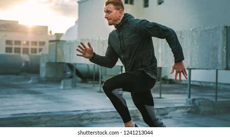 Side view of an athlete running on the rooftop of a building with sunflare in the background. Male athlete doing fitness workout on the terrace of a building at sunrise.