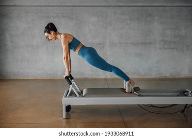 Side view of athletic Determined young woman in sportswear performing plank position on a Pilates Reformer Machine Bed in gym. Training at big industrial loft studio.