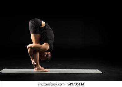 Side view of athletic man practicing yoga in Uttanasana or The Standing Forward Bend Pose isolated on black