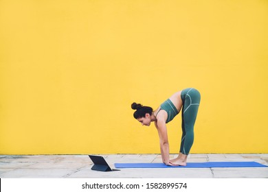 Side view of athletic slim sportswoman bending forward and stretching body looking at tablet screen with yoga video tutorial standing on mat against yellow wall
