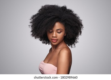 Side view of attractive African American female with perfect skin and curly hair looking down after spa procedure against gray background