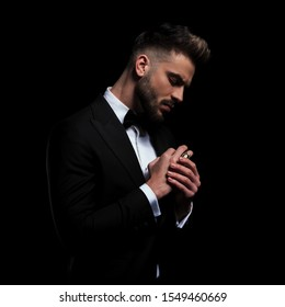 side view of an attractive businessman wearing black tuxedo standing and fixing his ring on black studio background