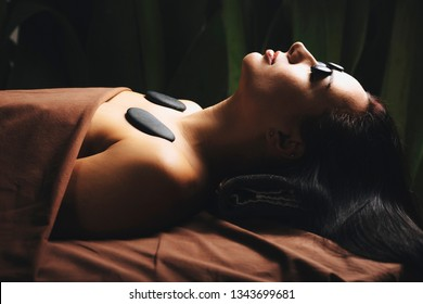 Side view of a attractive caucasian girl leaning on a spa bed with hot volcanic stones on her eyes and shoulder ina spa wellens salon.