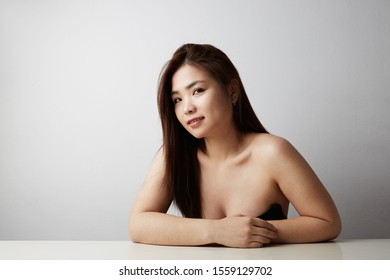 Side view of attractive Chinese woman posing on the white background. Isolated.