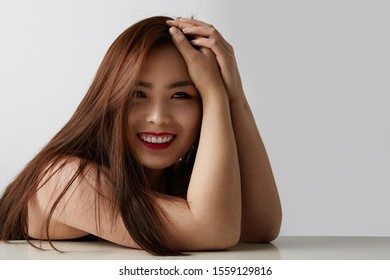 Side view of attractive Chinese woman posing on the white background and smiling. Isolated.