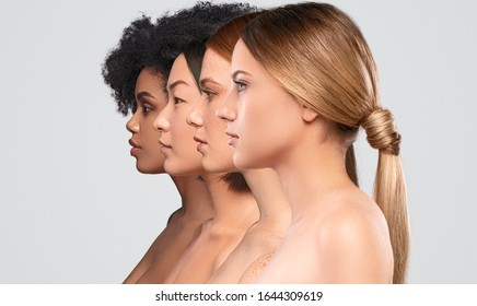 Side view of attractive diverse ladies standing in line while representing spa industry against gray background