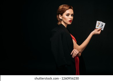 side view of attractive girl in red dress and black jacket holding poker cards and looking at camera isolated on black