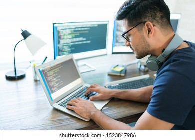 Side view of attractive Hispanic developer programming software using computer while working from home