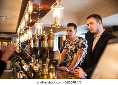 Side view of attractive male friends drinking beer at bar or pub
