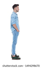 side view of attractive man holding hands in his pockets wearing denim, standing isolated on white background; full body, full length