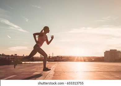 Side view of an attractive sporty girl is running on street during the sunset. Jogging.