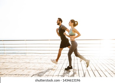 Side view of an attractive sporty young fitness couple wearing sportswear jogging together at the beach