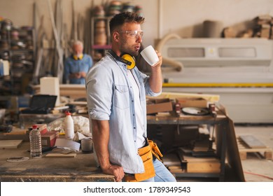 Side view of an attractive stylish craftsman holding coffee mug and sipping coffee in his carpentry workshop