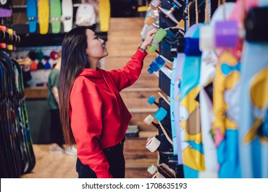 Side view of attractive teenage woman choosing longboard from store rack during Black Friday sales, youthful Chinese hipster girl spending day for buying skateboard and practicing hobby skills