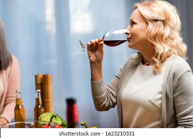 side view of attractive woman drinking wine from wine glass