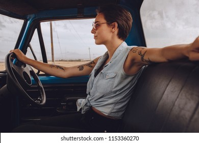 Side view of attractive woman driving an old truck. Female going on a road trip in countryside.