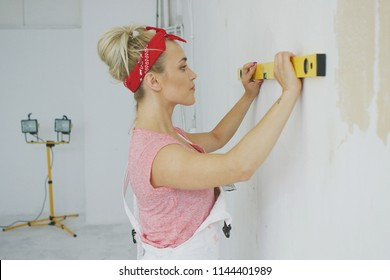 Side view of attractive young blond female in light overalls and red headband concentrating on checking white unpainted wall with bubble level