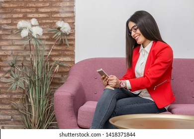 Side view of attractive young pretty woman smiling and holding mobile phone sitting on pink coach
