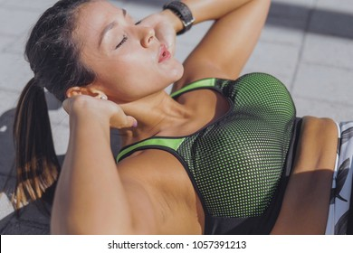 Side view of attractive young woman lying on pavement and exercising abdominal muscles in the park.