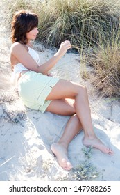 Side view of an attractive young woman relaxing on the sun dunes of a beach, touching and feeling the nature vegetation and being thoughtful during a sunny day on vacation.