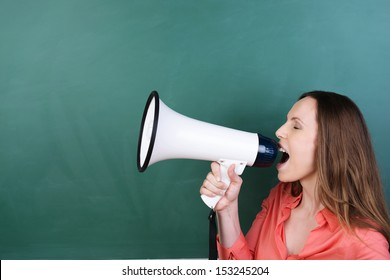 Side view of an attractive young woman standing in front of a blank green blackboard with copyspace yelling into a megaphone