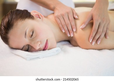 Side view of an attractive young woman receiving shoulder massage at spa center