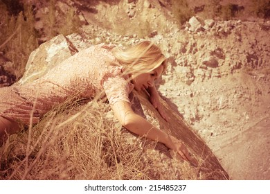 Side view of an attractive young woman laying on a coastal dark and textured rock mountain