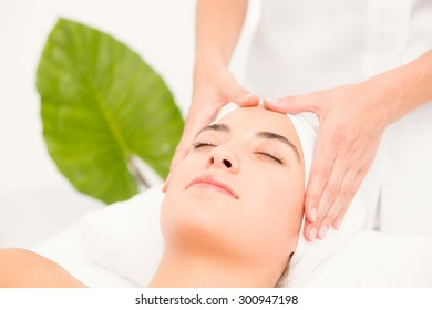 Side view of an attractive young woman receiving facial massage at spa center