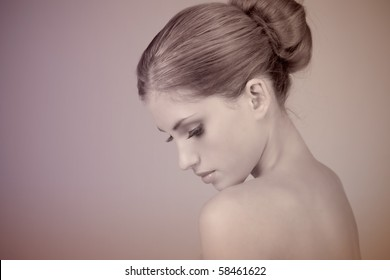Side view of attractive young woman wearing a hair bun. She is pensively looking down. Horizontal shot.