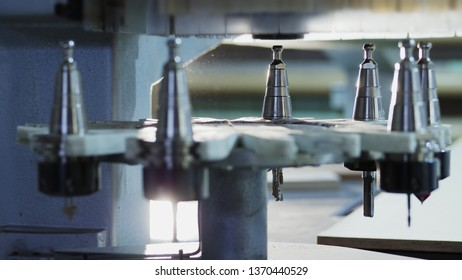Side view: Automatic change of milling heads. Modern CNC machining center for milling wooden products. Closeup of milling heads change