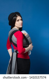 Side view of babywearing attractive young mother with baby in woven wrap carrier. Free hands and active motherhood concept idea